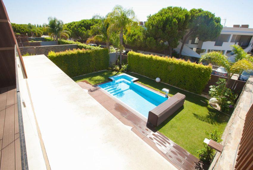 vista da varanda para jardim e piscina