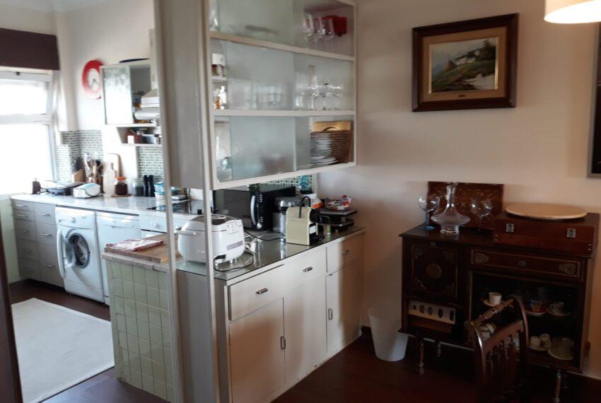 Parte zona refeições e cozinha aberta